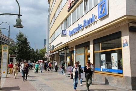 bank branch: BERLIN, GERMANY - AUGUST 27, 2014: People walk by Deutsche Bank branch in Berlin. Deutsche Bank is one of largest banks in the world with 98,200 employees (2013).