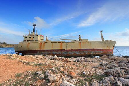 ashore: Cyprus - Mediterranean Sea coast. Rusty shipwreck washed ashore. Stock Photo