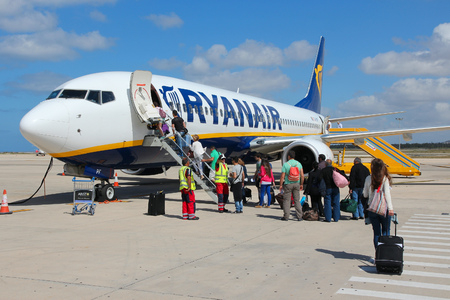net income: PAPHOS, CYPRUS - MAY 18, 2014: Passengers board Ryanair Boeing 737-800 aircraft in Paphos. Ryanair had 866.7 million EUR of net income in financial year ending March 2015. Editorial