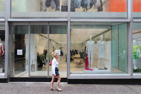 1 person: NEW YORK, USA - JULY 1, 2013: Person walks by Elie Tahari store in 5th Avenue, New York. Elie Tahari is an Iranian-American fashion designer and his brand brings USD 500 million in annual revenue.