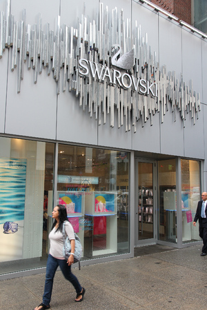 swarovski: NEW YORK, USA - JULY 1, 2013: People walk by Swarovski store in New York. Swarovski brand exists since 1895 and has 24,841 employees (Dec 2009).