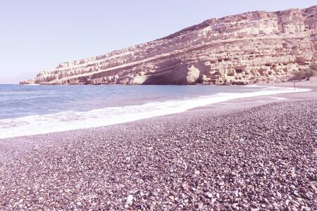 neolithic: Coast of Crete island in Greece. Pebbly beach of famous Matala. There are old Neolithic caves in the limestone rock. Retro style - filtered colors.