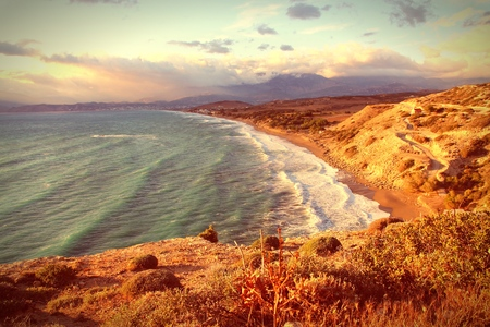 beach landscape: Landscape of Crete island in Greece. Kommos - sandy beach near Matala and Kalamaki. Sunset light. Vintage style - filtered colors. Stock Photo