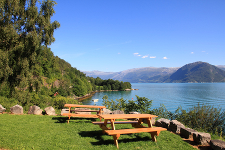 hardanger: Norway bench with view. Picnic tables by Hardanger Fiord. Stock Photo