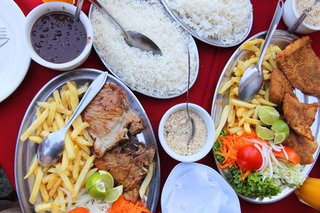 fish and chips: Cocina brasile�a - la parrilla de carne y pescado con frijoles negros, papas fritas, farofa y arroz.