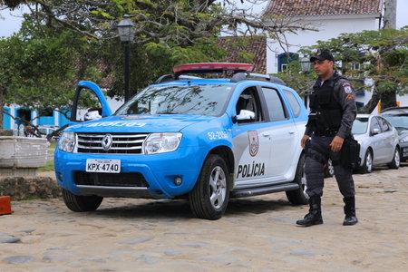 Paraty, Brazilië - 14 oktober 2014: Politieman loopt naast Renault Duster politieauto in Paraty (staat van Rio de Janeiro). PMERJ staatspolitie werk aan 52.000 mensen.