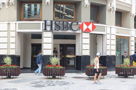 trillion: CURITIBA, BRAZIL - OCTOBER 7, 2014: People walk by HSBC bank in Curitiba, Brazil. HSBC is one of largest bank groups, holding assets of $2.69 trillion worldwide (2012).