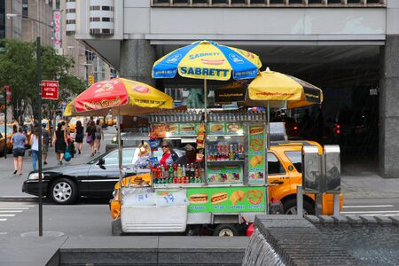 merchant: NEW YORK, USA - JULY 4, 2013: Vendor sells hot dogs next to 6th Avenue in New York. It is estimated that Americans eat some 20 billion hot dogs a year (NHDSC data).