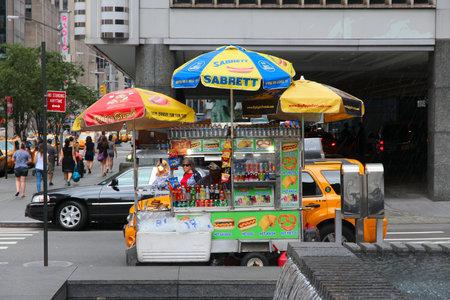 perro caliente: NUEVA YORK, EE.UU. - 04 de julio 2013: El vendedor vende perros calientes junto a la avenida sexta en Nueva York. Se estima que los estadounidenses comen algunos 20 mil millones de perros calientes al a�o (datos NHDSC). Editorial