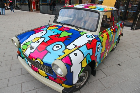 despite: BERLIN, GERMANY - AUGUST 25, 2014: Colorful Trabant 601 car parked in Berlin. 3,096,099 Trabant cars were produced despite their infamous inefficiency and outdated technology.