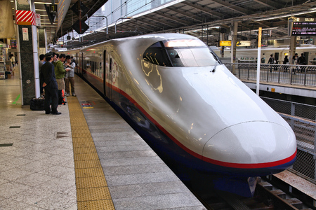 fastest: TOKYO, JAPAN - MAY 4, 2012: Travelers board Shinkansen Hayate train at Tokyo Station. Hayate has top operating speed of 275kmh and is among fastest trains worldwide.