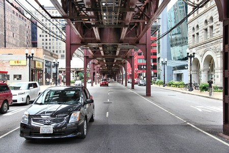 chicago city: CHICAGO, USA - JUNE 28, 2013: Cars drive under elevated train tracks in Chicago. Chicago is the 3rd most populous US city with 2.7 million residents (8.7 million in its urban area). Editorial