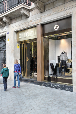 gucci shop: BARCELONA, SPAIN - NOVEMBER 6, 2012: People walk by Gucci fashion shop in Barcelona, Spain. The fashion company founded in 1921 is among most recognized luxury brands in the world.