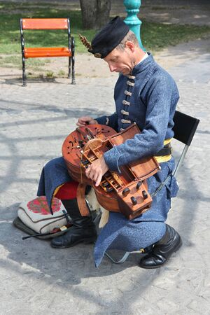 fiddle: BUDAPEST, HUNGARY - JUNE 20, 2014: Street performer plays hurdy-gurdy in Budapest. Hurdy-gurdy is a traditional string instrument also known as wheel fiddle. Editorial