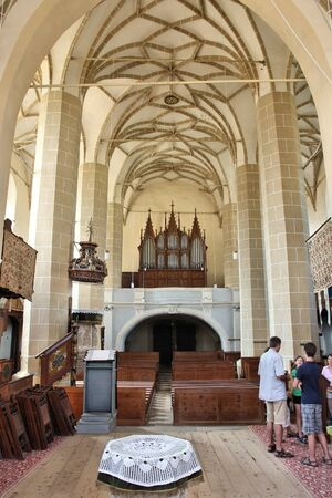 biertan: BIERTAN, ROMANIA - AUGUST 25, 2012: People visit medieval fortified church interior in Biertan, Romania. The church was completed in 1524 and is a UNESCO World Heritage Site.