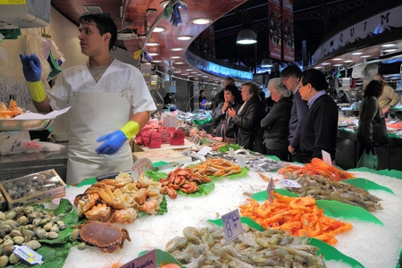 boqueria: BARCELONA, SPAIN - NOVEMBER 6, 2012: People visit Boqueria market in Barcelona, Spain. The marketplace in Ciutat Vella district dates back to year 1217. Editorial