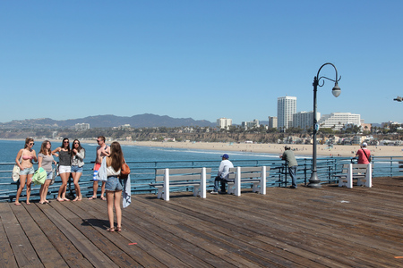santa monica: SANTA MONICA, UNITED STATES - APRIL 6, 2014: People visit the pier in Santa Monica, California. As of 2012 more than 7 million visitors from outside of LA county visited Santa Monica annually.