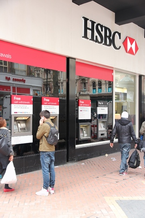 trillion: BIRMINGHAM, UK - APRIL 19, 2013: People walk by HSBC Bank in Birmingham, UK. HSBC is one of largest bank groups, holding assets of $2.69 trillion worldwide (2012).