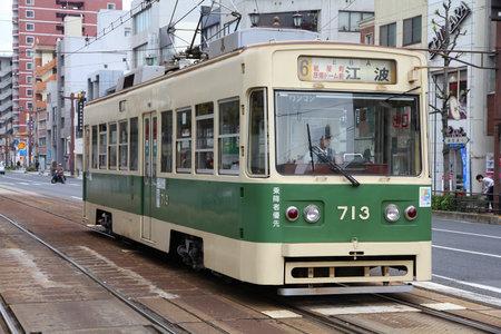 honshu: HIROSHIMA, JAPAN - APRIL 21, 2012: People ride public Hiroden tram in Hiroshima, Japan. The tram line celebrated its 100th anniversary on May 11, 2012.