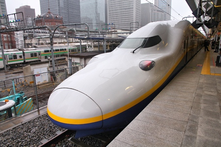 locomotives: TOKYO, JAPAN - MAY 4, 2012: Travelers board Tohoku Shinkansen E4 series train at Tokyo Station. Hayate has top operating speed of 275kmh and is among fastest trains worldwide.