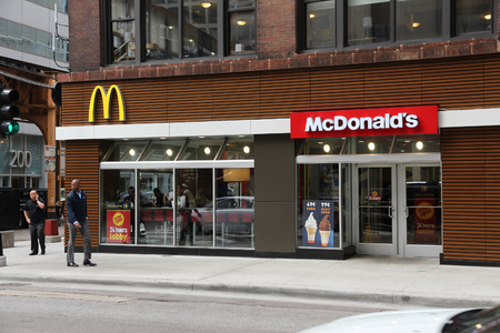 chicago: CHICAGO, USA - JUNE 26, 2013: Person walks by McDonalds restaurant in Chicago. McDonalds is the 2nd most successful restaurant franchise in the world with 33,000 locations.