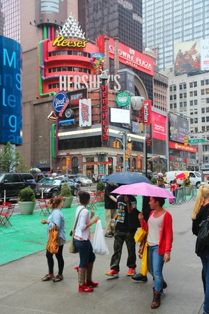 hersheys: NEW YORK, USA - JUNE 10, 2013: Tourists and local people visit rainy Times Square in New York. The square at junction of Broadway and 7th Avenue has some 39 million visitors anually. Editorial