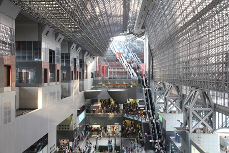 existed: KYOTO, JAPAN - APRIL 18, 2012: Travelers hurry at Kyoto Station in Kyoto, Japan. It is Japans 2nd biggest train station building. The building is recent, but station existed here since 1877. Editorial