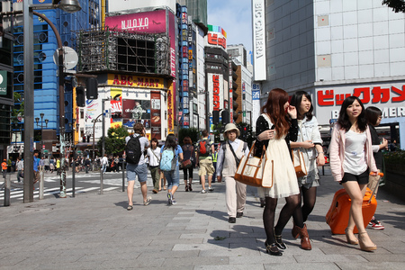 populous: TOKYO, JAPAN - MAY 11, 2012: People walk in Shinjuku district of Tokyo. Tokyo is the capital city of Japan and the most populous metropolitan area in the world with almost 36 million people.