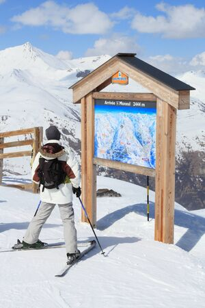 ski runs: VALLOIRE, FRANCE - MARCH 24, 2015: Skier analyzes ski map in Galibier-Thabor station in France. The station is located in Valmeinier and Valloire and has 150km of ski runs.