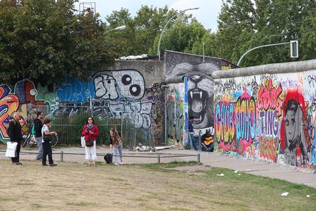 iron curtain: BERLIN, GERMANY - AUGUST 26, 2014: People visit the Berlin Wall (Berliner Mauer). Iconic iron curtain border divided Berlin in years 1961-1989.