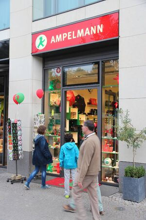 conceived: BERLIN, GERMANY - AUGUST 25, 2014: People visit Ampelmann souvenir store in Berlin. Ampelmann is the pedestrian light symbol in Berlin. It was conceived in 1961.