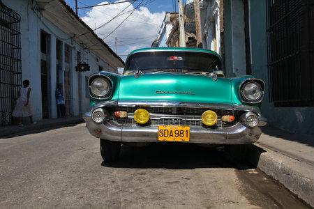 capita: SANCTI SPIRITUS, CUBA - FEBRUARY 7, 2011: People walk past yank tank oldtimer car in Sancti Spiritus. Cuba has one of lowest vehicle per capita rates in the world (38 per 1000 citizens in 2008).