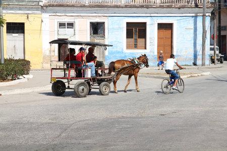 capita: SANCTI SPIRITUS, CUBA - FEBRUARY 6, 2011: Cubans ride horse-drawn cart on in Sancti Spiritus, Cuba. Cuba has one of lowest vehicle per capita rates in the world (38 per 1000 citizens in 2008). Editorial