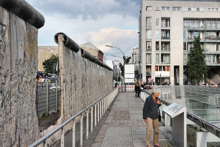 existed: BERLIN, GERMANY - AUGUST 26, 2014: People visit historical Berlin Wall. Berlin Wall was a historical barrier that existed from 1961 through 1989.