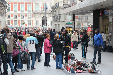 counterfeit: MADRID, SPAIN - OCTOBER 24, 2012: Street vendors sell illegal counterfeit goods in Madrid. Madrid is a popular tourism destinations with 3.9 million estimated annual visitors (official data).