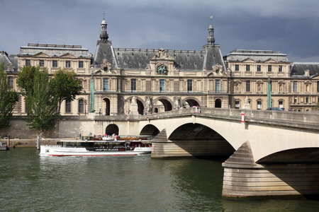 carrousel: PARIS, FRANCE - JULY 20, 2011: People ride a sightseeing boat under Pont du Carrousel in Paris. Paris is the most visited city in the world with 15.6 million international arrivals in 2011.