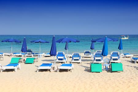 Cyprus beach sunbeds - sandy warm weather place. Makronissos Beach.
