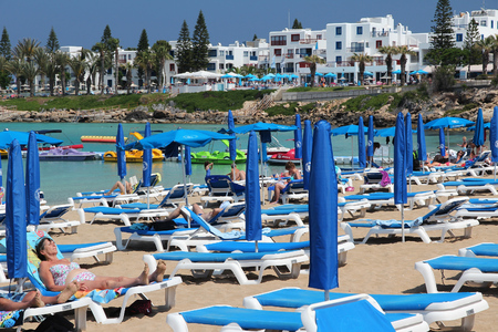 cyprus tree: PROTARAS, CYPRUS - MAY 17, 2014: People relax at Fig Tree Bay in Protaras, Cyprus. Tourism makes about 10 percent of Cyprus budget with 2.4 million annual arrivals (2011).