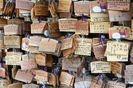 TOKYO, JAPAN - APRIL 12, 2012: Ema, traditional wooden prayer boards in front of Ueno Toshogu Shrine in Taito ward of Tokyo. Kami (the spirits of gods) receive the wishes.