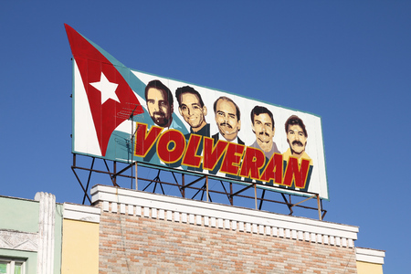 detained: CIENFUEGOS, CUBA - FEBRUARY 3, 2011: Propaganda billboard in the street in Cienfuegos, Cuba. The billboard depicts five Cubans detained by the US. Cuba claims theyre innocent.