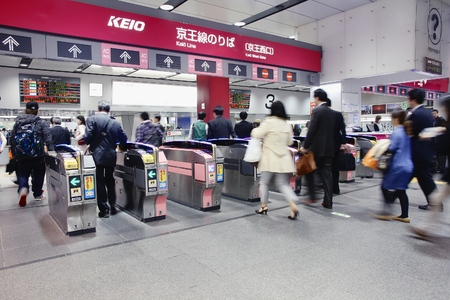 schlagbaum: TOKYO, JAPAN - APRIL 13, 2012: Passengers hurry at Shinjuku Station in Tokyo. It is the worlds busiest transport hub with daily usage by up to 3.64 million people. Editorial