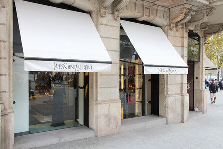 laurent: BARCELONA, SPAIN - NOVEMBER 6, 2012: Person walks by Yves Saint Laurent fashion shop in Barcelona. YSL is a famous luxury fashion brand founded in 1962. It had 473 million EUR revenue in 2012.
