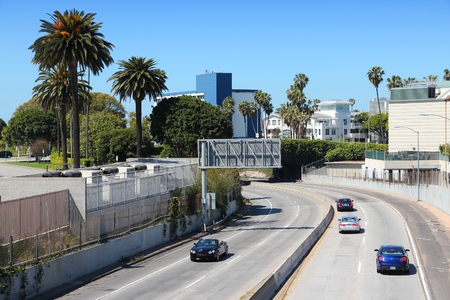 santa monica: SANTA MONICA, UNITED STATES - APRIL 6, 2014: People drive Interstate 10 highway in Santa Monica, California. The freeway is part of 47,856 miles long Interstate Highway System.