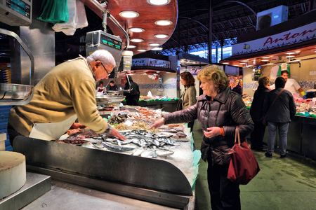 city fish market: BARCELONA, SPAIN - NOVEMBER 6, 2012: People visit seafood shop at Boqueria market in Barcelona, Spain. The marketplace in Ciutat Vella district dates back to year 1217. Editorial