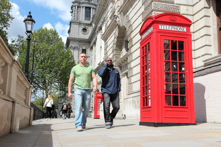 phonebooth: LONDON, UK - MAY 16, 2012: People walk by red telephone booth in London. With more than 14 million international arrivals in 2009, London is the most visited city in the world (Euromonitor).