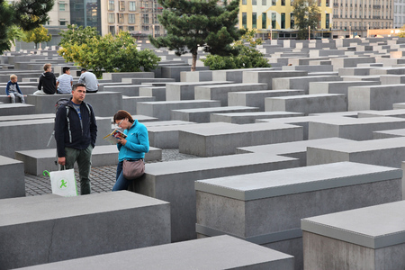 holocaust: BERLIN, GERMANY - AUGUST 26, 2014: People visit Holocaust Memorial in Berlin. Berlin is Germanys largest city with population of 3.5 million.