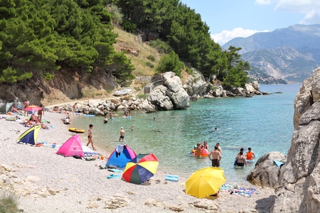 vacationers: DALMATIA, CROATIA - JUNE 28, 2011: Vacationers enjoy the beach in Marusici, Dalmatia, Croatia. In 2011 11.2 million tourists visited Croatia, most of them in summer.