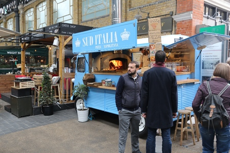 existed: LONDON, UK - APRIL 22, 2016: People visit a food truck in Old Spitalfields Market in London. A market existed here for at least 350 years.