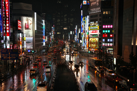 rain japan: TOKYO, JAPAN - MAY 9, 2012: People drive in the rain in Shinjuku district, Tokyo. Shinjuku is one of special wards of Tokyo. 337,556 people live here. Editorial