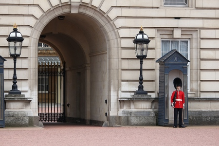 a watchman: LONDON, UK - APRIL 23, 2016: Queens Guard soldier stands in front of Buckingham Palace in London, UK. The guards in traditional uniforms are important symbol of the UK.